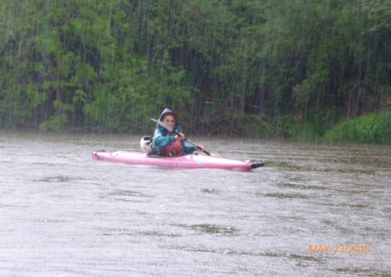 Kayaker paddling in rain