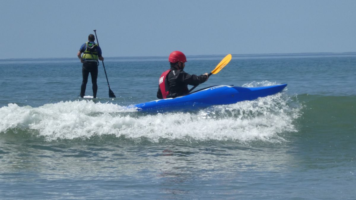 kayaker falling off a wave